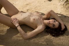 Стройная красотка нежится  на песке